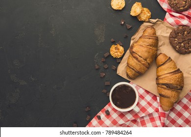 French croissants and coffee background. Top view on freshly baked pastry and spices on rustic wood with copy space. Tasty breakfast concept, mockup for recipe or culinary book
