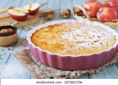 French cuisine. Apple clafoutis pie with praline in ceramic dish for sweet dessert and fresh apples on blue background