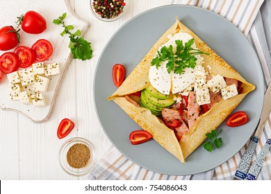 French cuisine. Breakfast, lunch, snacks. Pancakes with egg poached, feta cheese, fried ham, avocado and tomatoes on white table. Top view