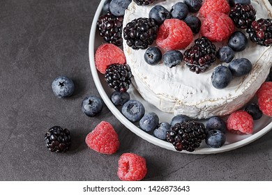 French delicacy. Elegant Camembert. Soft cheese with white mold with wild berries on a plate.  Round Camembert with raspberries, blackberries and blueberries. Healthy and tasty Breakfast. Top view.