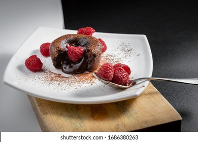 French dessert, chocolate volcano or coulant on a white plate, baked cake with delicious melted chocolate and several raspberries