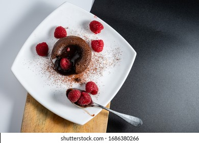 French dessert, chocolate volcano or coulant on a white plate, baked cake with delicious melted chocolate and several raspberries.