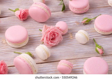 French dessert macarons and rose flower. Pink and white almond cookie. Close up view.