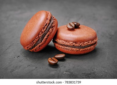 French dessert. Sweet brown chocolate macaroons or macarons with coffee flavor and beans on black concrete background