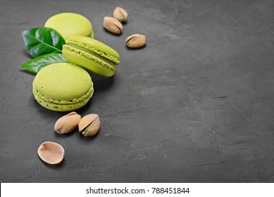French dessert. Sweet green pistachio flavor macaroons or macarons with nuts and leaves on black concrete background