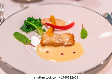 French dish hors d'oeuvre with yellow and red bell peppers with salad and white sauce of breaded fish on a silver rim white dinner plate.