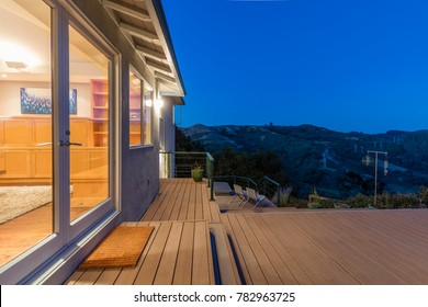 French doors and Wooden Deck with outdoor patio at night with amazing hillside view