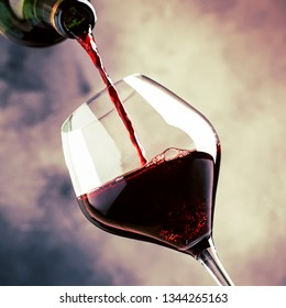 French dry red wine, pours into glass, gray background, selective focus