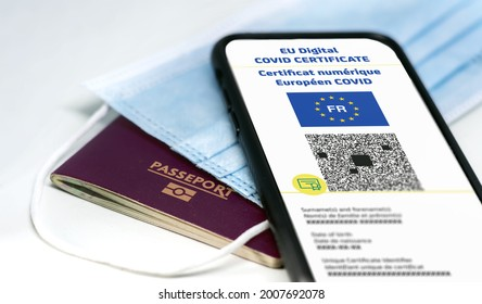 """French EU Digital COVID Certificate with the QR code. Translation from french """"European COVID digital certificate"""". Mobile phone over a surgical mask and a french passport. Health passport"""