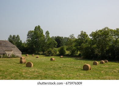 French farm in Normandy with fresh haystacks.