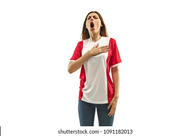 French female fan celebrating on white background. The young woman in soccer football uniform as winner standing and singing a hymn isolated at white studio. Fan, support concept. Human emotions