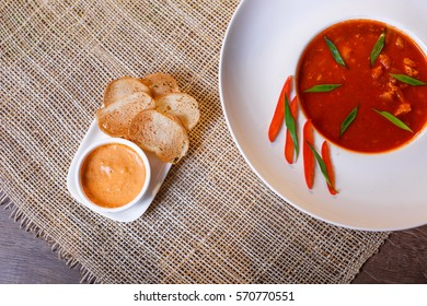 French fish soup Bouillabaisse served with pepper mayonnaise, toasted baguette and grated cheese. Selected focus on the upper part of the plate and the toasts.