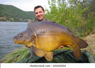 French fisherman holding a giant mirror carp.