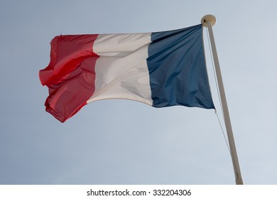 The French flag against blue cloudy sky.
