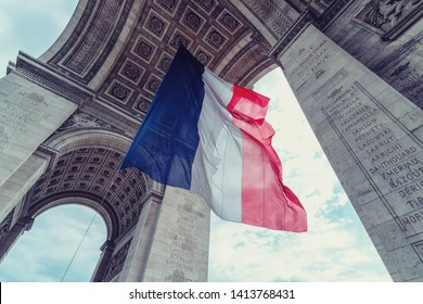 french flag at arc de triomphe during bastille day