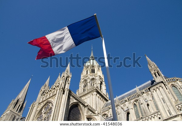 French flag flies in foreground against Bayeux Cathedral