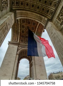 French flag flying under the Arc de Triomphe in Paris, France