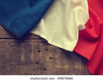 French flag on a rustic wooden background with space for text or image, vintage color stylized