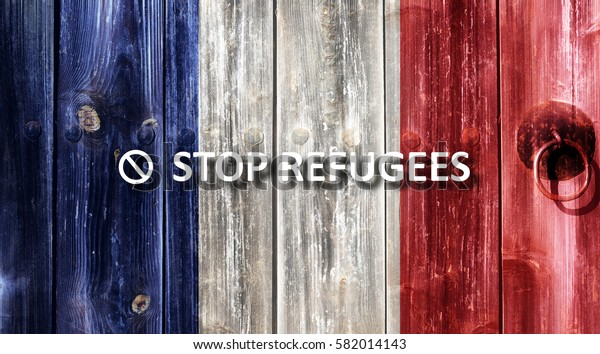 French flag painted on an old wooden door. Next to the door handle text Stop Refugees.
