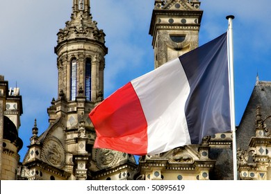 The French flag waves dramatically in front of the ornate towers of the Chateau at Chambord.