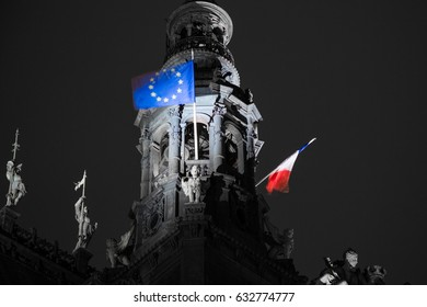 French flag waving over city hall in Paris, France. Flag of European Union on the Hotel de Ville. Selective focus. Elections in France.