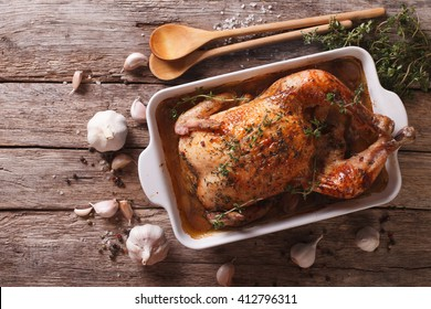 French Food: Chicken with forty cloves of garlic in the dish for baking and ingredients close-up on the table. horizontal view from above