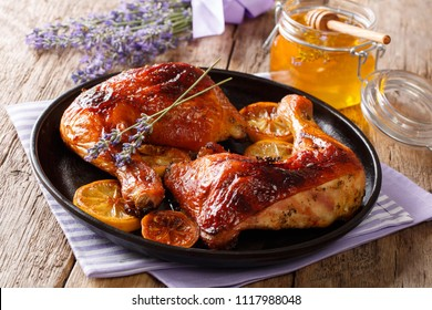 French food: fried quarters chicken legs with lavender honey, spices and lemon close-up on a plate on the table. horizontal