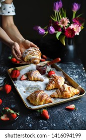 French fresh homemade croissants with strawberry jam on the rustic black dark background. Woman holds a croissant