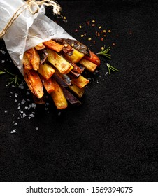 French fries,  baked fries from different types and colors of potatoes sprinkled with herbs and spices on a black background, top view, copy space