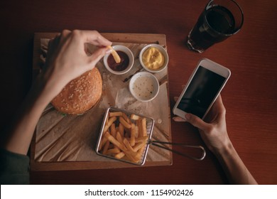 French fries and barbeque sauce on wooden tray. Woman eating burger and chips in cafe while holding her mobile phone using an application to send an sms message in her smartphone device while eating.