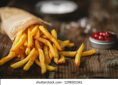 French fries in a basket with ketchup and salt on a dark background