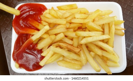 French fries in a bowl with ketchup sos on dark table, top view
