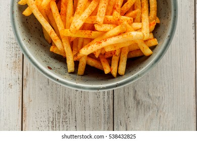 French fries in a bowl on a wooden background.