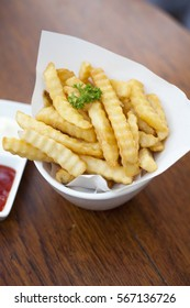 French fries in a bowl on a wooden table