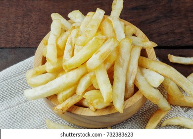 French fries in bowl on wooden with closeup.