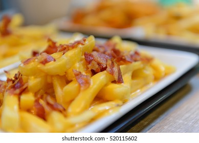 French fries and cheese with bacon on top  in a white bowl
