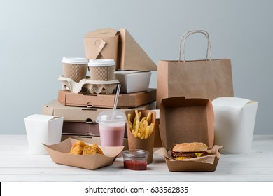 French fries, chicken Nuggets, hamburger, milkshake, sauce, latte and coffee. Pizza boxes and paper bag, light wooden background. Fast food delivery.