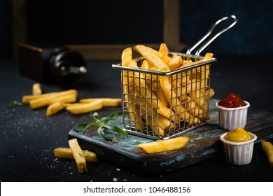 French fries close up with condiments on dark background