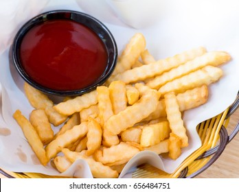 French fries. Close up of fried potatoes with tomato sauce bottle in a black plastic wicker basket on wooden table. Traditional of french fries thai style. - Snack and fast food concept.