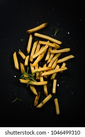 French fries close up with salt and rosemary on dark background