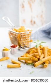 French fries close-up with condiments on white background