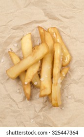 french fries with coarse salt on brown paper