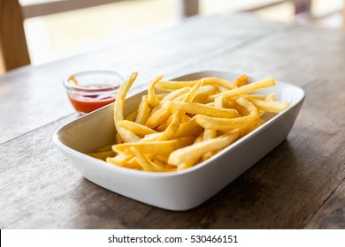 French fries dish on the table, focusing.