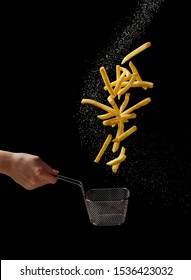 French fries - fried potatoes flying out of basket in hand, fly fastfood isolated on black background