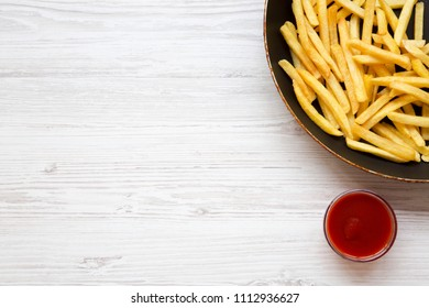 French fries in a frying pan with ketchup on a white wooden table, top view. Copy space.
