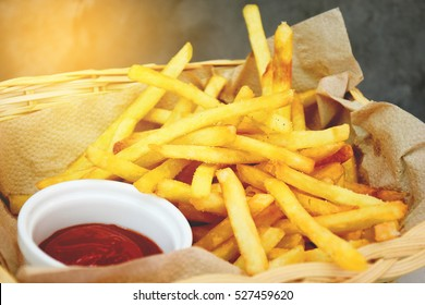 French fries and ketchup in basket with flare light
