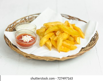 French fries with ketchup and mayonnaise on the rattan plate