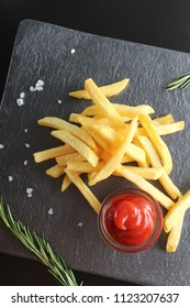 french fries and ketchup on a dark background