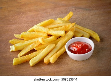 French fries with ketchup on a wooden background.
