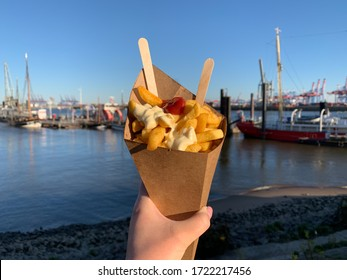 French fries with mayonnaise and ketchup in a recyclable paper bag with wooden fork in female hand on a background of river Elbe and cranes in port of Hamburg